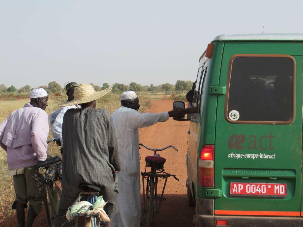 Eine Gruppe Menschen diskutiert mit den Insassen eines grünen Kleinbusses von AEI