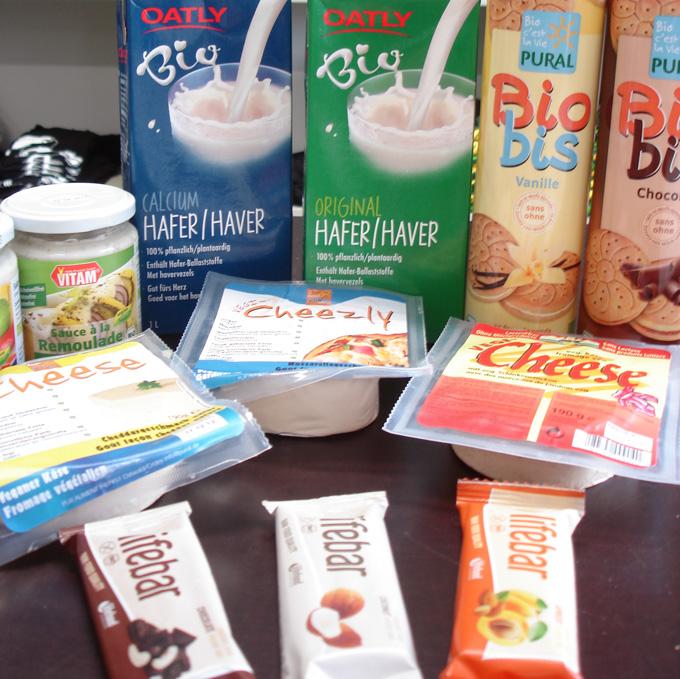 Auf dem Bild ist eine Auswahl von veganen Produkten aus dem veganladen zu sehen, veganer Käse, vegane Rohkostriegel, vegane Kekse, Hafermilch und Mayo