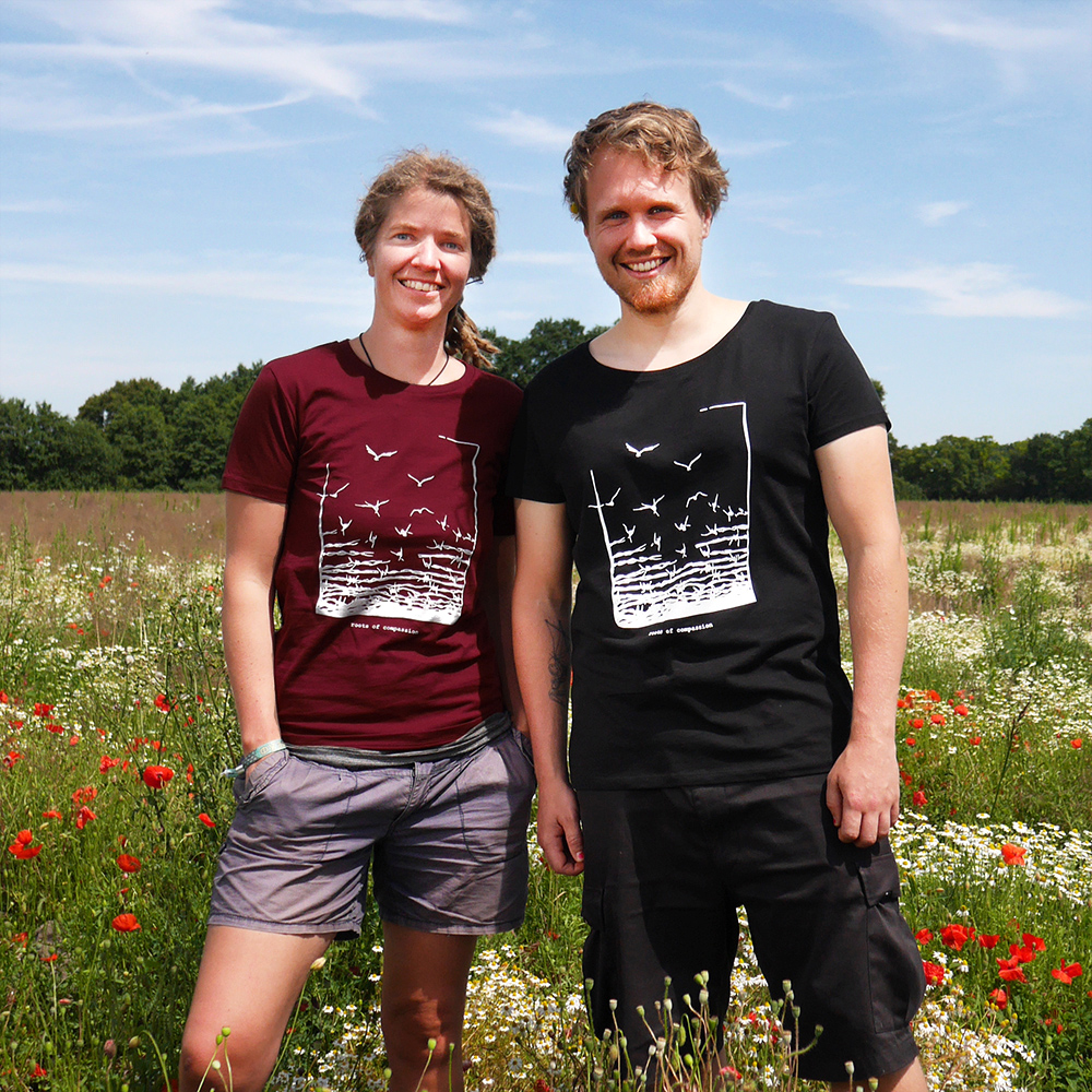 New colours for the 'Freedom'-T-shirt: red and black, worn by Julia and Alex standing in the field next to our door.