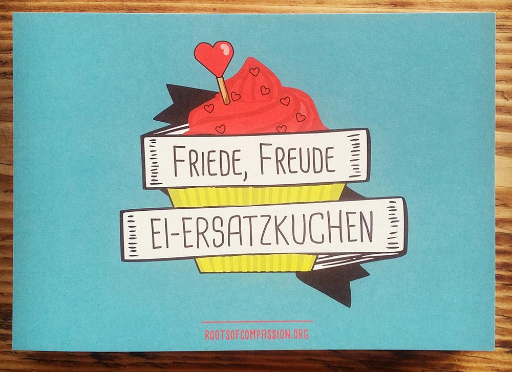 Bild einer Postkarte mit dem Spruch 'Friede, Freude, Eiersatzkuchen', geschrieben auf einer Banderole vor einem Cupcake