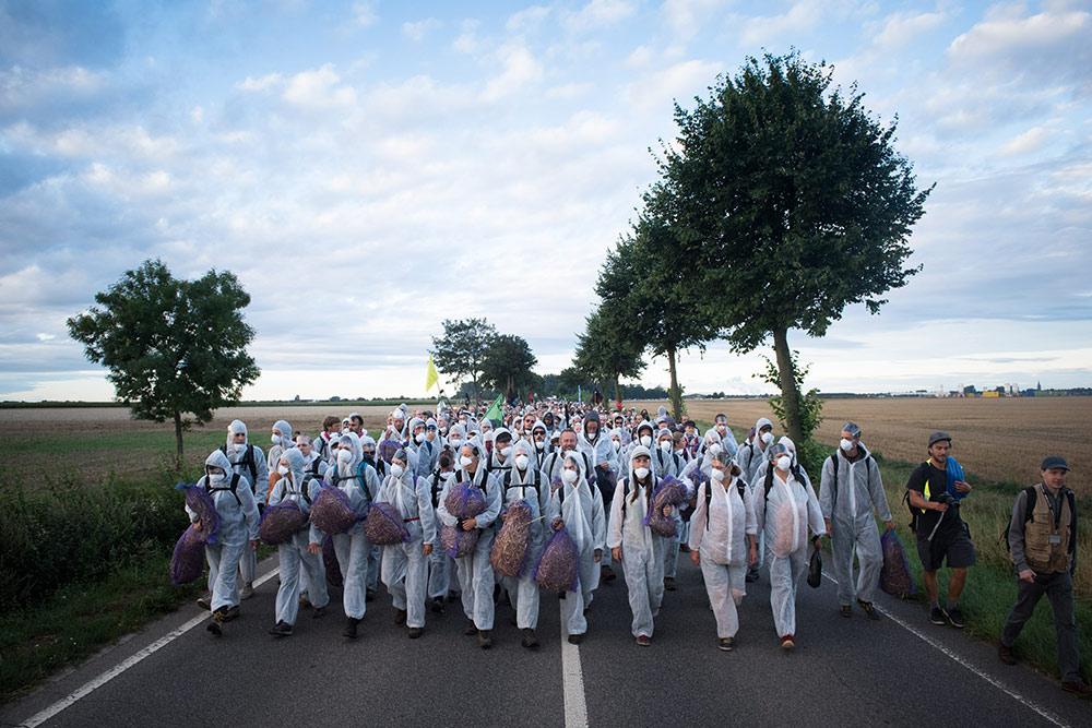 Eine große Gruppe Menschen in weißen Schutzanzügen ist auf einer Landstraße auf dem Weg zu einer Aktion.