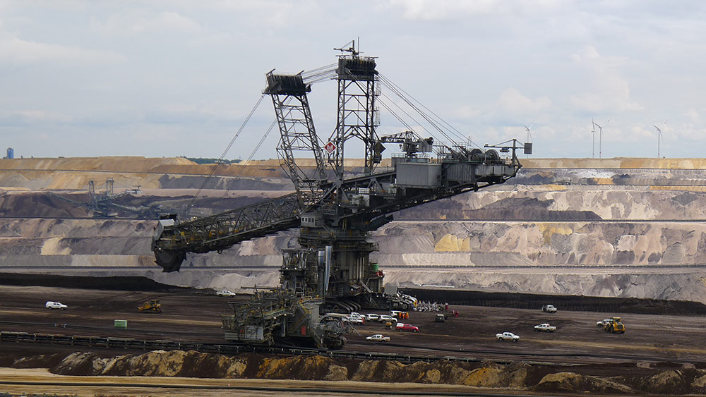 Eine Gruppe von Aktivist*innen hat sich vor einem mächtigen Tagebaubagger versammelt.