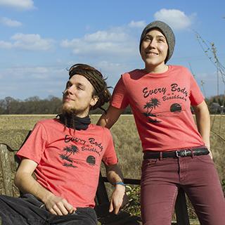 Deni und Simon sitzen mit unseren neuen 'Every body is a beachbody-T-Shirts auf der Bank vor unserem Lager