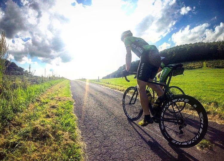 Radfahrer fährt bergauf der Sonne entgegen