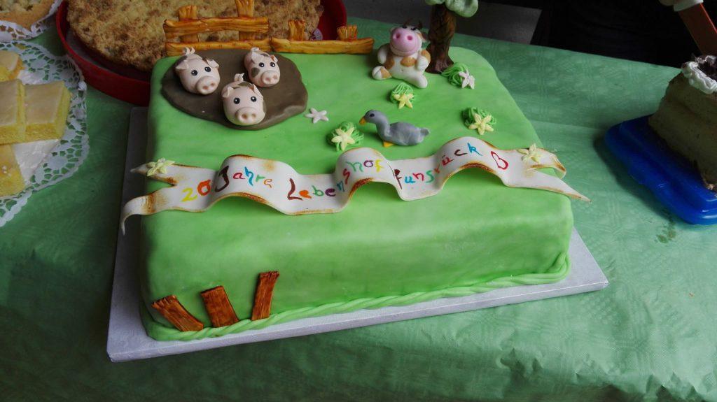 Jubiläumstorte für den Lebenshof Hunsrück, mit Schweinen, Kuh und Enten auf der Torte sowie dem schriftzug zum 20jährigen Jubiläum