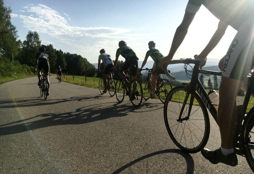 Radteam in hügeligem Gelände bei blauem Himmel auf der Abfahrt