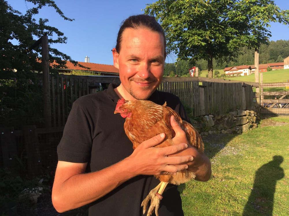 Marco Mehring mit einem Huhn auf dem Arm
