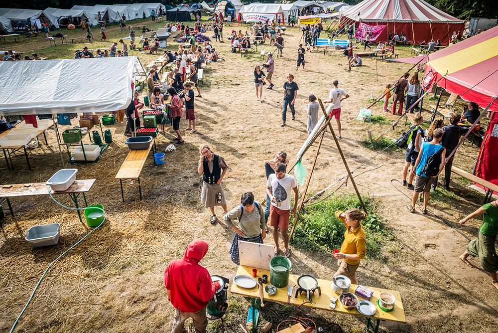 KLimacamp von schräg oben mit Zelten zum Schlafen und für Workshops und vielen Menschen, die dort allerlei Tätigkeiten nachgehen