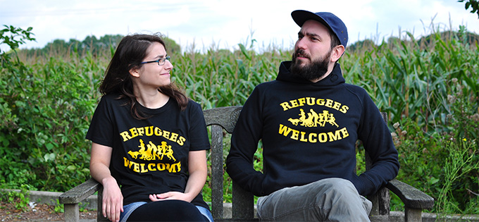 Maria and Sania are sitting on a bench wearing the new Refugees Welcome clothes