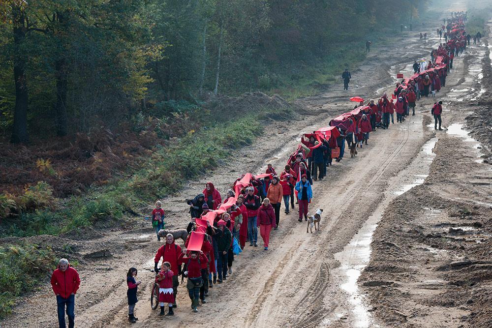 Menschen in rot bzw. mit roten Bannern, die eine rote Linie auf einem unbefestigten Weg bilden.