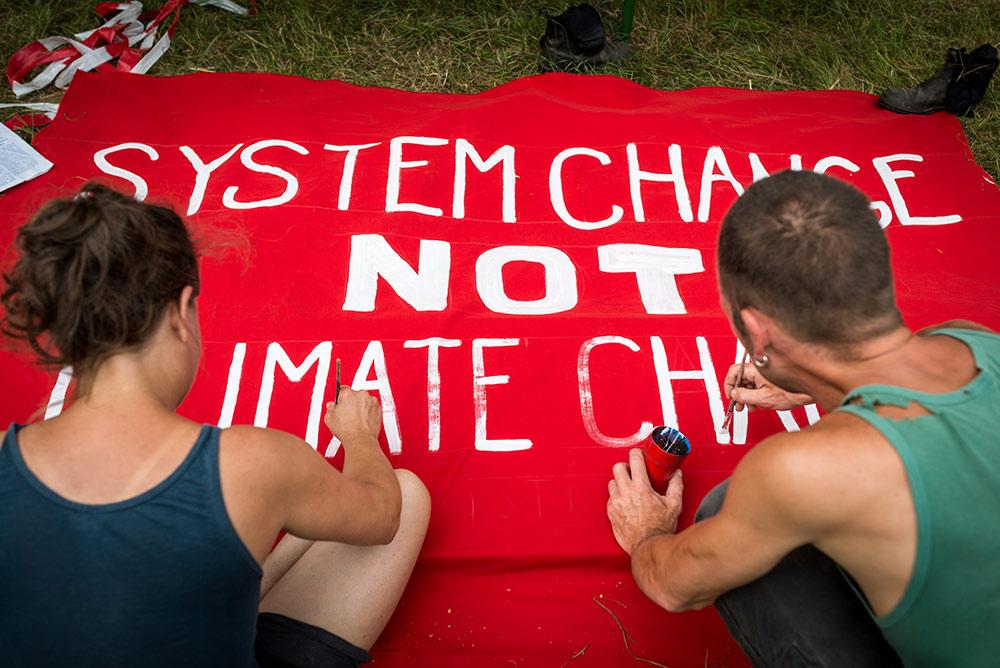 Zwei Menschen malen auf einem roten Plakat den Spruch 'System Change Not CLimate Change'.