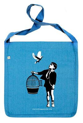 Open cage Tasche von roots of compassion - hellblaue Tasche mit langen Henkeln und Druckverschluss aus recyceltem Stoff und PET-Flaschen. Motiv: EIn Junge, der eine Taube aus einem Käfig befreit.