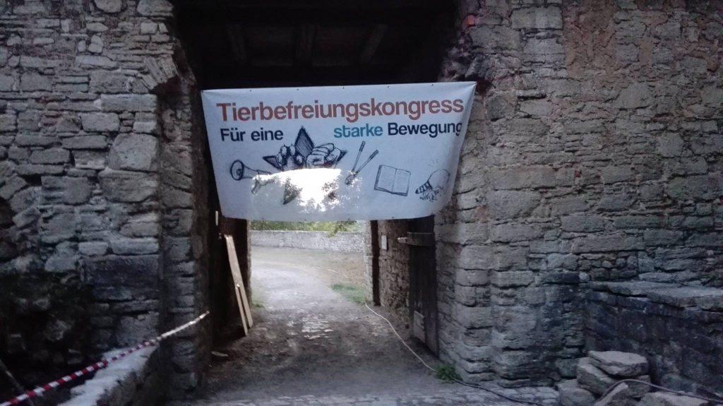 Eingang durchs Burgtor zum Tierbefreiungskongress. Das Banner weht im Wind.