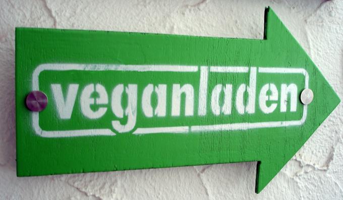 Ein grünes Schild in Pfeilform, das in Richtung des veganladens weist.